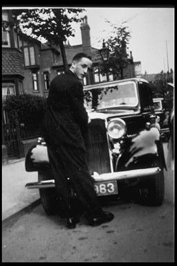 A picture of a young man stood in front of a car