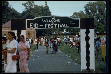 A picture of a home made wooden entrance to the park with lots of people milling around in saree and traditional dress