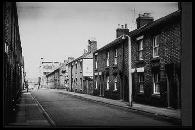 A picture of a road with terraced housing on each side.  In the distance is a large building