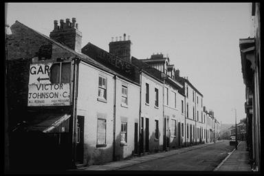 A picture looking up a road of terraced houses.  An old, broken hording is on the gable end of the first house.