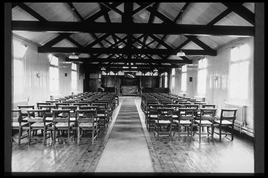 A picture of a long wide hall with open rafters.  Chairs are set on either side with a passageway between them
