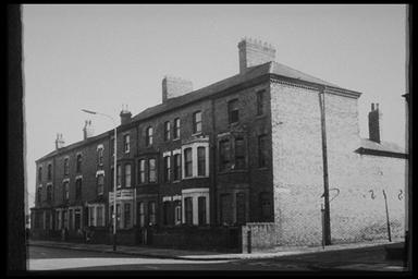 A picture of a long row of derelict three story terraced houses