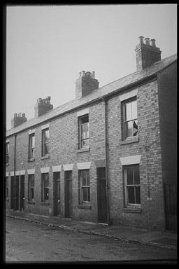A picture of a row of small derelict terraced houses with broken windows