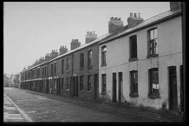 A picture of a long row of small derelict terraced houses