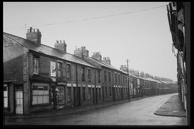 A picture of a long row of terraced houses on a road that curves to the right.  There is a corner shop at the nearest end of the row