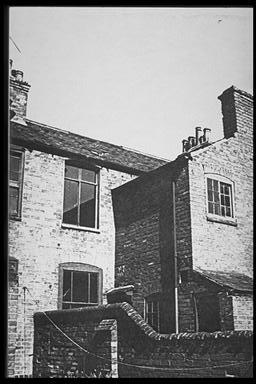 A picture of the back of a terraced house, showing the wall surrounding the back yard
