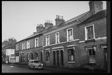 A picture of a row of terraced houses with a car parked in front