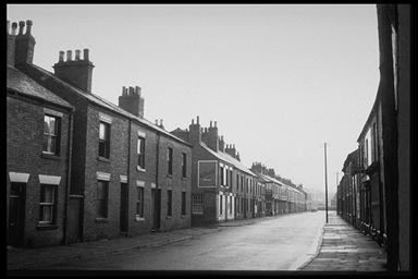 A picture of a long, deserted road with rows of terraced houses either side