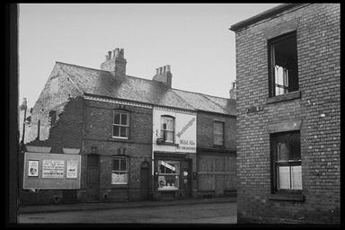 A picture of three terraced houses.  One still occupied, the next is a shop and the third is boarded up