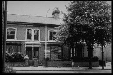 A picture of the front of a row of terraced houses with a large tree at the front