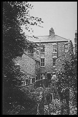 A picture of the rear of a three story house with an overgrown garden
