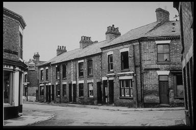 A picture of derelict terraced houses at the junction of three roads