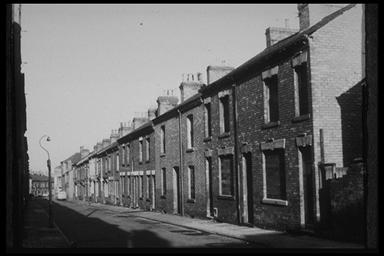 A picture of a long row of boarded up terraced houses
