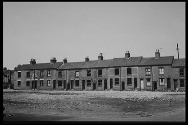 A picture of a long row of derelict terraced houses with a large piece of waste ground at the front
