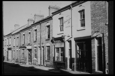 A picture of a row of terraced houses, one of which has been rendered and an advert for Kimberley Ales painted on it