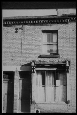 A picture of the front of a terraced house with a large downstairs window and a small upstairs one