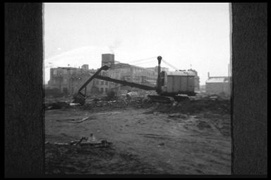 A picture of a large crane surrounded by derilict land with the remains of a patially demolished factory in the background