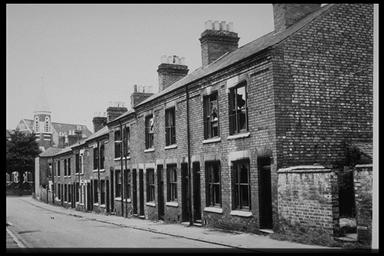 A picture of a row of derelict terraced houses leading down a gentle slope