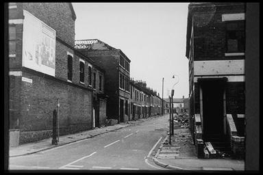 A picture of a long row of terraced houses with rubble in the street