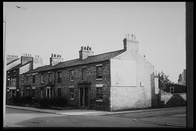A picture of a row of terraced houses with a large hoarding on the gable end of the first house