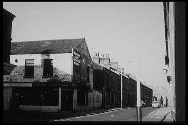 A picture of an old row of terraced houses with a shop on one corner with large adverts on the front wall