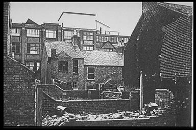 A picture of the rear of partially demolished terraced houses showing a large factory in the background