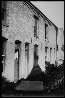A picture of a row of abandoned cottages.  There is an old mattress lying in the cobbled street