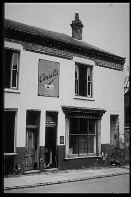 A picture of an abandoned terraced shop with two doorways to the left