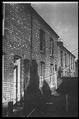 A picture of a row of abandoned terraced houses.  Washing lines are still attached to the walls