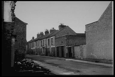A picture of a row of derelict terraced houses leading up a gentle slope