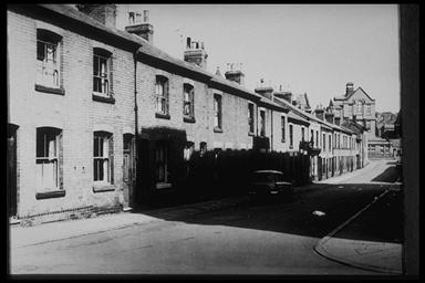 A picture of a row of derelict terraced houses leading down a gentle slope with a large factory building at the end of the road