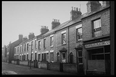 A picture of a row of terraced houses with small front gardens.  There is a shop at the begining of the row; 'Highfields Plating Co.'