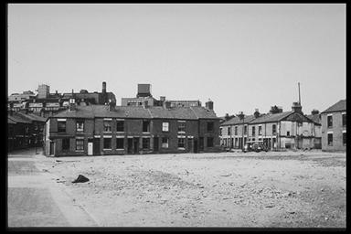 A picture of a row of old terraced houses with a large piece of waste ground in front covered in rubble