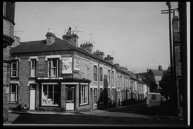 A picture of a small road junction showing terraced houses on each side.  There is a shop on the corner