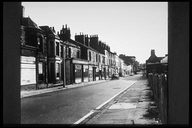 A picture of a road with terraced houses on either side, most of which are boarded up