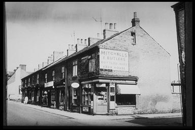 A picture of a row of terraced shops with a large Mitchells and Butler sign on the gable wall end