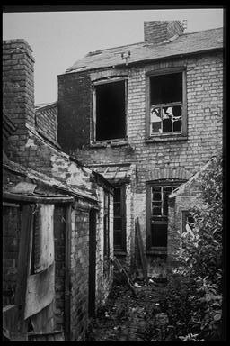 A picture of the back of some derelict terrace houses