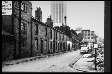 A picture of a road with a row of empty boarded up terraced houses on one side and rubble on the other