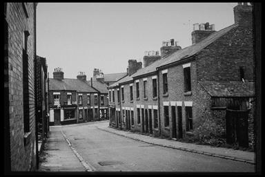 A picture of a road bending around to the right with a row of empty boarded up terraced houses
