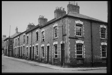 A picture of the corner of a row of terraced houses with large chimney pots and sash windows