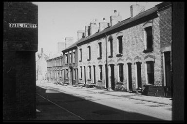 A picture of a row of derelict terraced houses.  On the side of the nearest house is a road sign saying Basil Street