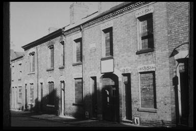 A picture of empty, boarded up terraced houses