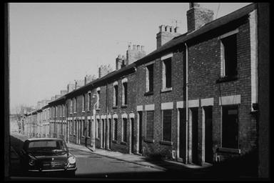 A picture of a long row of derelict terraced houses with a car parked outside.