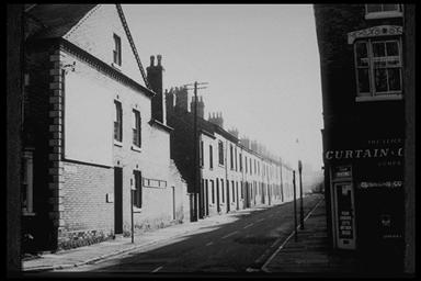 A picture of a long row of terraced houses with a shop on the corner that sold curtains