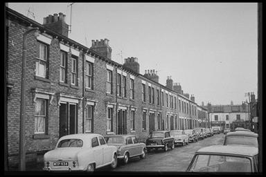 A picture of a row of terraced houses with cars parked all along the road