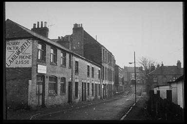 A picture of a row of empty, boarded up terraced houses with an advert for Kilworth hosiery on the gable end of the last house