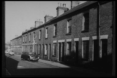 A picture of a row of empty, boarded up terraced houses with a number of cars parked on the road