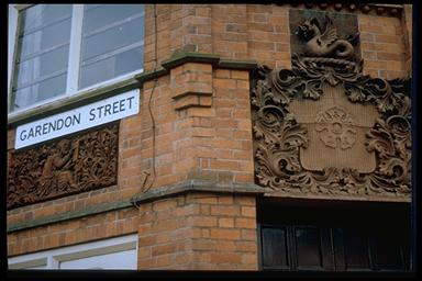 A picture of the street sign on the side of the library wall also showing stone filigree work