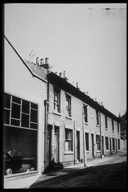 A picture of a row of terraced houses attached to a large showroom