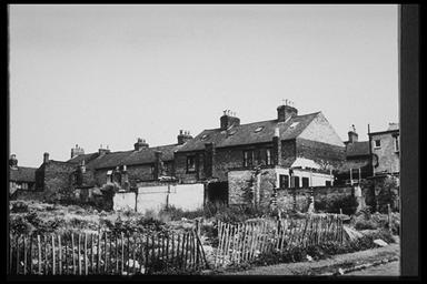 A picture of the back of ramshackle terraced housing backing onto waste ground